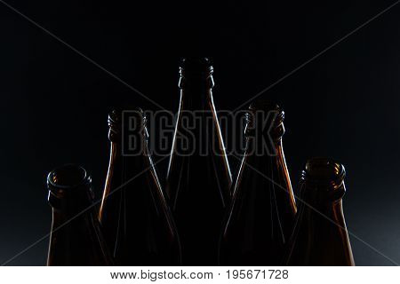 Silhouettes glass bottles for beer on a black background