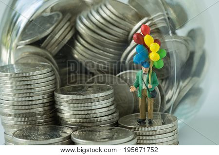 Miniature figure old man holding balloon standing on coins money in the jar as happy retirement saving concept.