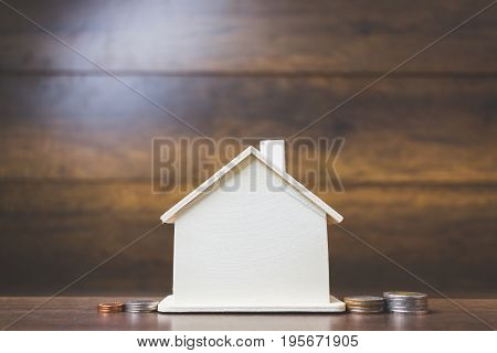 House models with stack coins on wooden table Business asset concept