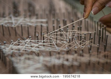 Loose End Tied Up To Wooden Board With Nails, Handcraft Textile Concept