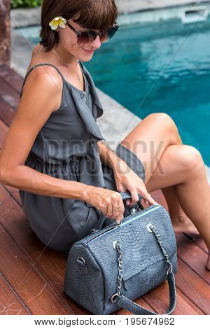 Fashionable woman holding luxury stylish snakeskin python bag. Elegant outfit. Close up of purse in hands of stylish lady. Model posing.