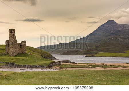 Assynt Peninsula Scotland - June 7 2012: Ruins of Castle Ardvreck at Loch Assynt with mountain in back under yellowish twilight sky. Green ground vegetation.