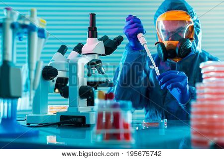 Research Of dangerous viruses in the laboratory. Prevention of a pandemic. A scientist in a biological protective suit works with a pipette