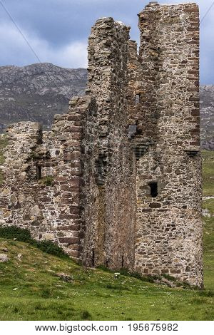 Assynt Peninsula Scotland - June 7 2012: Full frame closeup of one side of Brownish Ruins of Castle Ardvreck. Green ground vegetation. Blue sky.