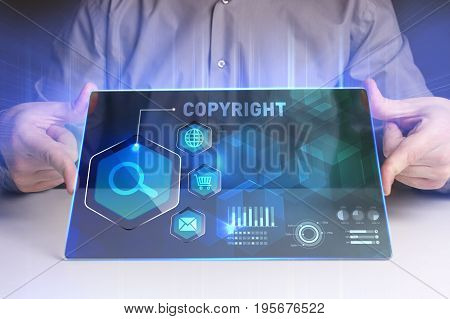 Business Technology Internet and network concept. Young businessman working on a virtual screen of the future and sees the inscription: Copyright