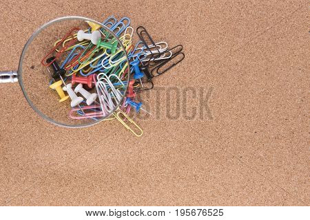 Background image of a magnifying glass over colourful paperclips and drawing pins