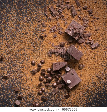 Chocolate background. Pieces and drops of chocolate cocoa powder on black.