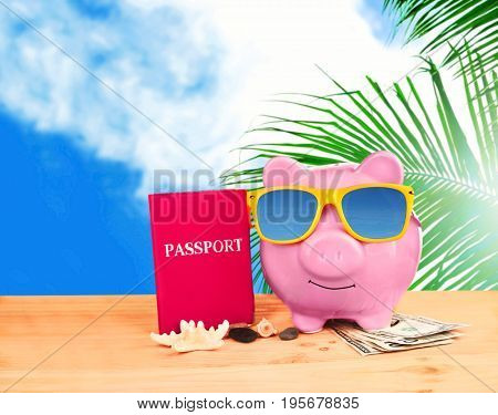 Piggy bank with sunglasses, passport and money on wooden table against sky background. Concept of money for vacation