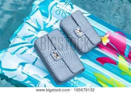 Woman luxury snakeskin python handbag in the swimming pool.