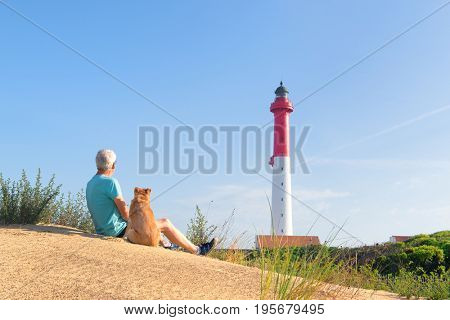 Man and his dog sitting on dune and looking to Lighthouse red and white at the French west beach