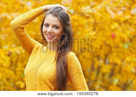 Young smiling brunette posing in autumn park on yellow trees background