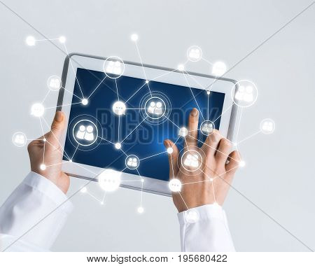 Tablet pc device with connection lines on screen in hands of doctor