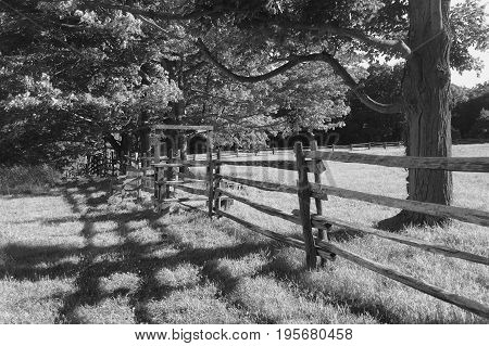Shadow and light with the fence and stile in the farm