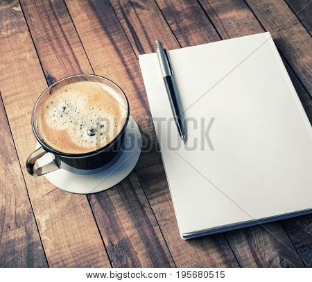 Blank closed book pencil and coffee cup on vintage wooden table background. Responsive design template.