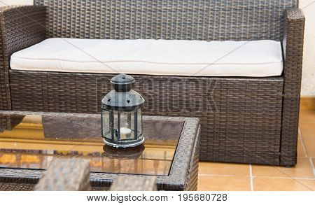 Rattan furniture sofa armchairs glass coffee table with candle holder fragment of patio porch mediterranean style terracotta floor tiles Spain