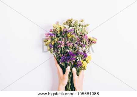 Female Hands Holding A Bouquet Of Multicolored Wildflowers