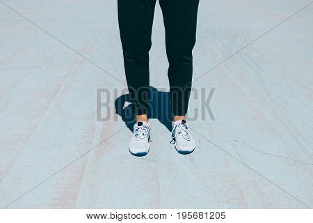 Female Legs In Black Pants And Sneakers On A Blue Concrete Court