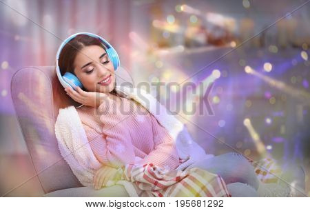 Young woman with headphones listening to music at home. Christmas and New Year songs