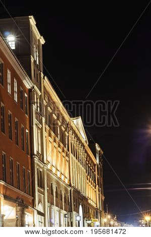 Street with a classicist building during the night in Poznan