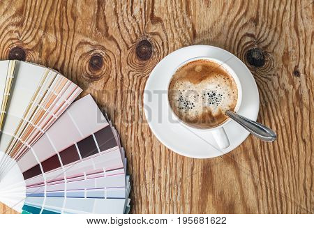 Color palette guide and coffee cup on wood table background. Sample colors catalog.