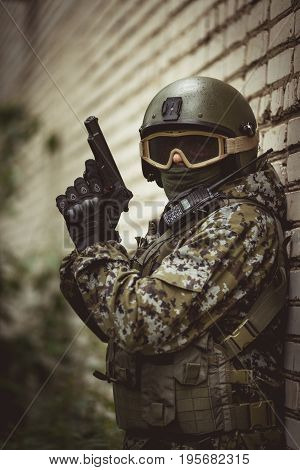 Military man in camouflage with helmet in military intelligence near brick building