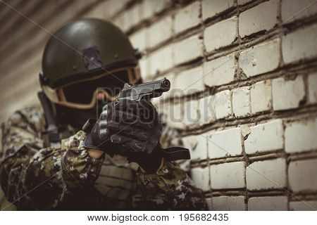 Strikeball player in camouflage with helmet on reconnaissance near brick building