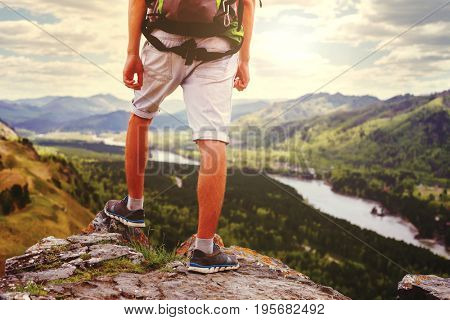 Young Man Traveler feet standing alone with  mountains on background. Lifestyle Travel concept outdoor