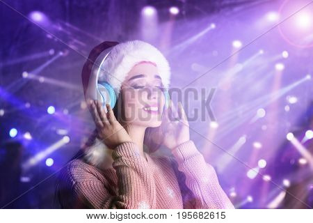 Young woman with headphones listening to music on blurred lights background. Christmas and New Year songs