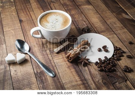 Photo of fresh tasty coffee on old wooden table background. Coffee cup cinnamon sticks coffee beans anise sugar spoon and coasters.