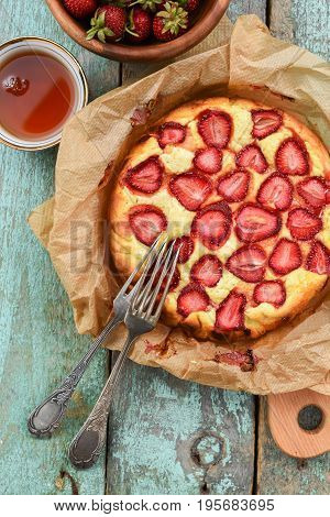 Homemade strawberry cake in baking paper with vintage melchior forks and black tea overhead view