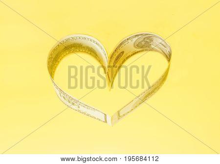 Dollar US bills in heart shape on yellow
