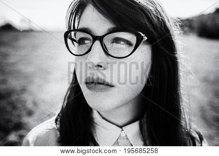 Outdoor close up portrait of young beautiful fashionable girl with long hair. Model wearing trendy round glasses, looking aside. Stylization for black and white film.