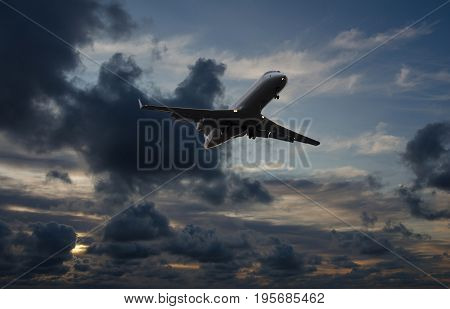 Airplane flying in sky with storm clouds at sunset time