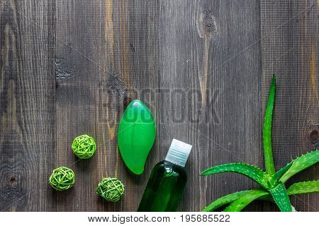 Homemade skin care. Aloe vera leafs, glass of aloe vera juice and soap on wooden table background top view.