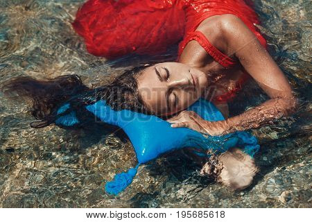 beautiful young woman in red dress laying down in water with pillow