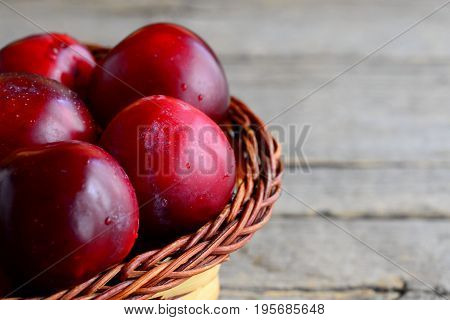 Fresh ripe plums in a wicker basket on a vintage wooden background. Plums closeup
