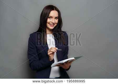 Busy elegant business woman in formal suit writing down notes to notepad, smiling at camera, gray studio background.