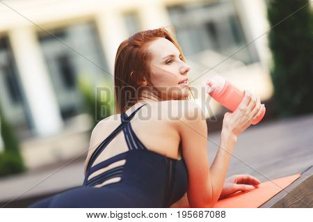 Photo of sports girl lying on rug in street against modern building background