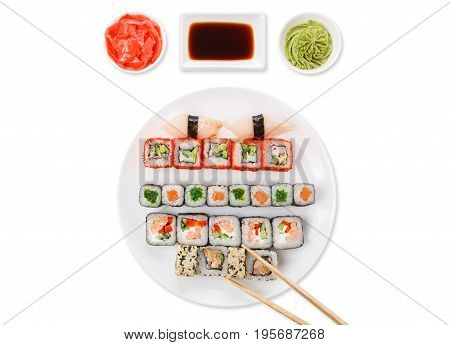 Japanese food restaurant. Sushi set served on white platter with soy sauce, ginger and wasabi and chopsticks picking one piece. Top view at white background with copy space