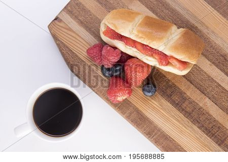 Brioche bun with strawberries, blueberries and raspberries on a chopping board with black coffee