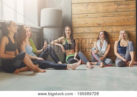 Girls in sportswear having rest after fitness training. Group of young fit women sitting and talking in sport club interior, pov. Sporty and healthy lifestyle concept