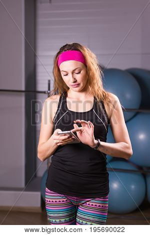 Young woman with fitness tracker in gym.