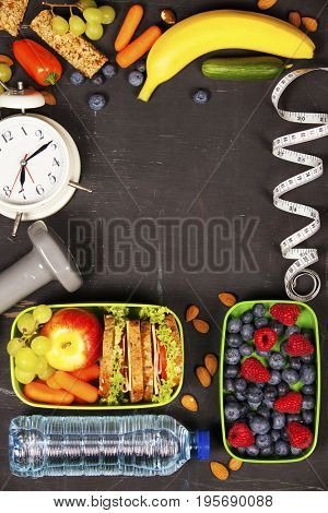 Health & Fitness Food in lunch boxes, measuring tape  and alarm clock on wooden board. Diet food, health and fitness concept