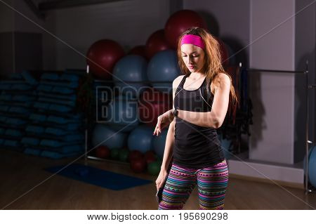 Happy young woman using activity tracker in fitness gym.
