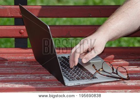 Closeup Of A Hands Busy Typing On A Laptop In The Park
