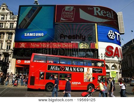 Piccadilly Circus in the spring with red bus in foreground