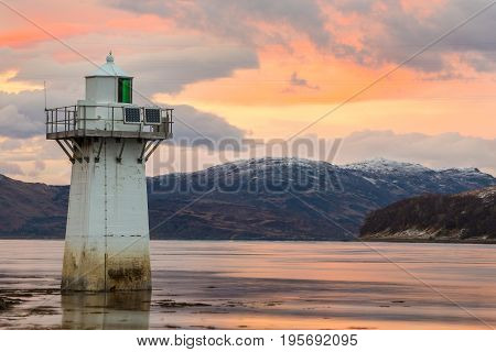 Lighthouse at Kylerhea where the the narrow water of Kyle Rhea and Loch Alsh separate the Isle of Skye from the Scottish mainland at sunset.