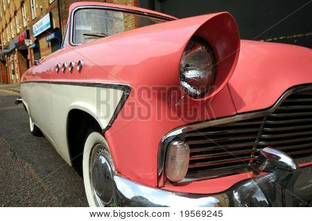 Stylish old pink car on an old street