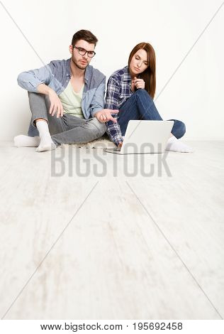 Couple talking and working together, man pointing at screen sitting on floor with laptop on white background at new apartment