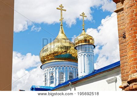 Golden domes of the Russian Orthodox Church against a blue sky with clouds